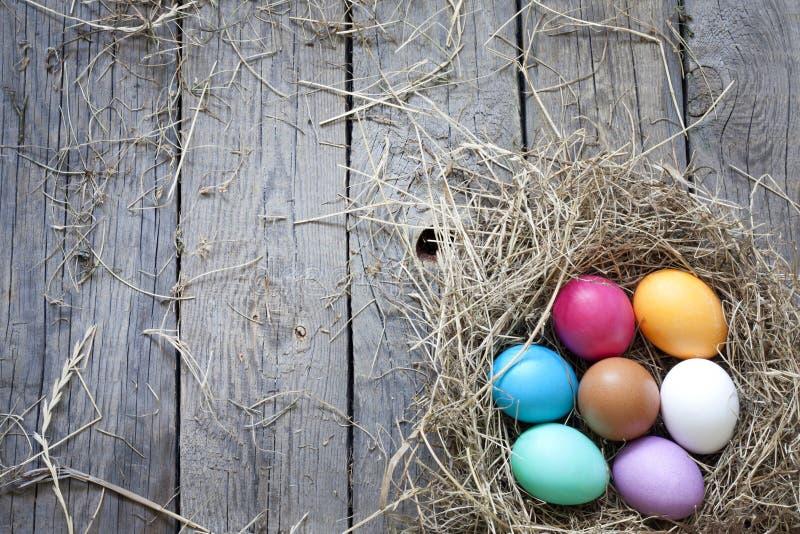 Ostereier im Nest auf hölzernen Vorständen der Weinlese stockbild