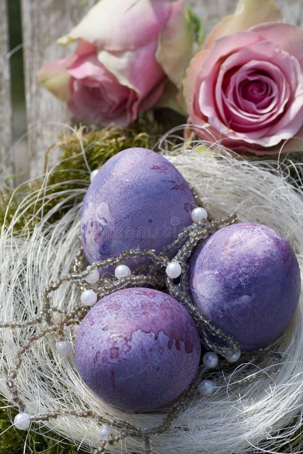 Ostereier im Purpur mit Rosen und Perlen stockbilder