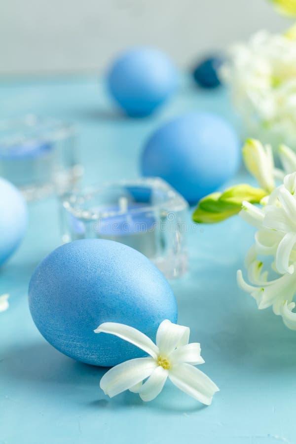 Ostereier, Kerzen und weiße Hyazinthe auf einem blauen Beton stockbild