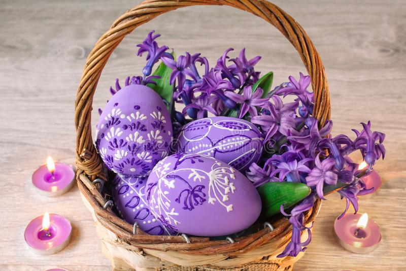 Ostereier malten in einem Korb mit Blumen in den lila Tönen und in den Kerzen herum auf einem hölzernen Hintergrund stockfoto