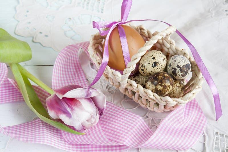 Ostereier mit Bändern in einem Weidenkorb, nahe bei der Tulpe stockbilder