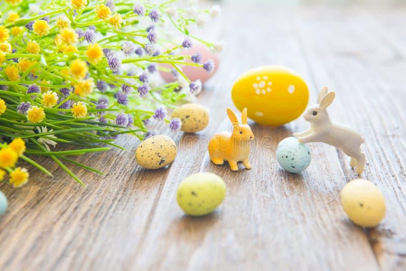 Ostereier mit Blumen und kleinen Häschenspielwaren auf hölzernem Brett, Ostern-Feiertagskonzept lizenzfreie stockfotos