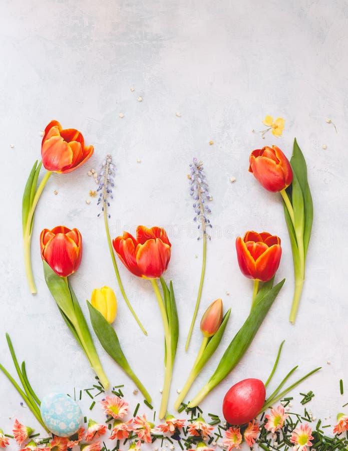 Ostereier mit Frühlingsblumen auf rustikaler Oberfläche lizenzfreie stockbilder