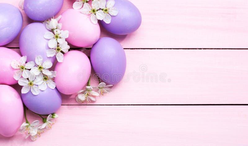 Ostereier und weiße Blumen Kirschblüte auf rosa Holztisch stockfoto