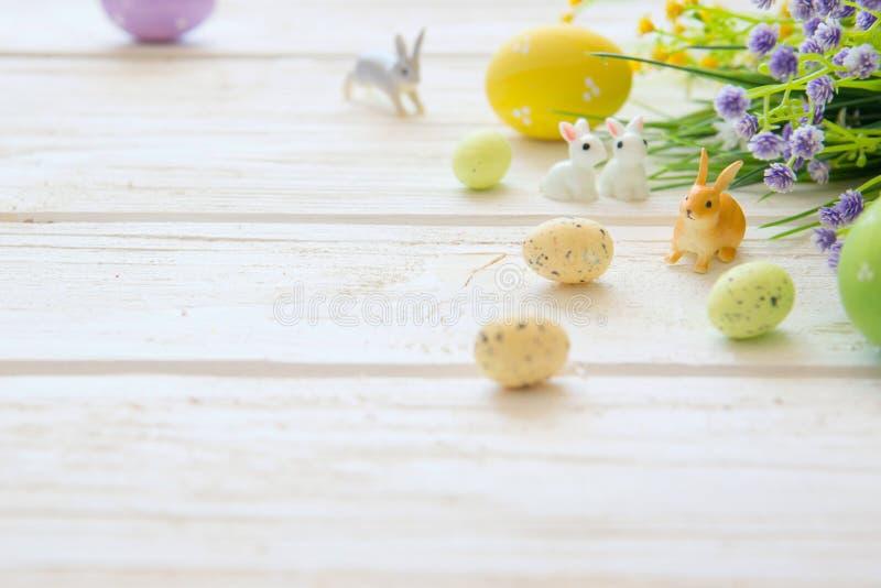 Ostereier und Zweig mit Blumen auf hölzernem Kaninchenspielwaren lizenzfreie stockbilder
