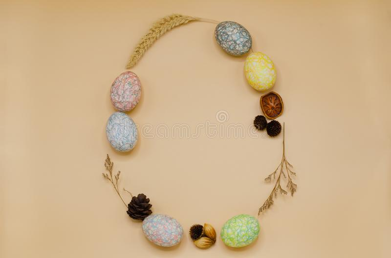 Ostereiform, die bunte haben, gemalte Eier vom Zeichenstift verzieren mit trockenen Blättern und Blumen lizenzfreies stockbild