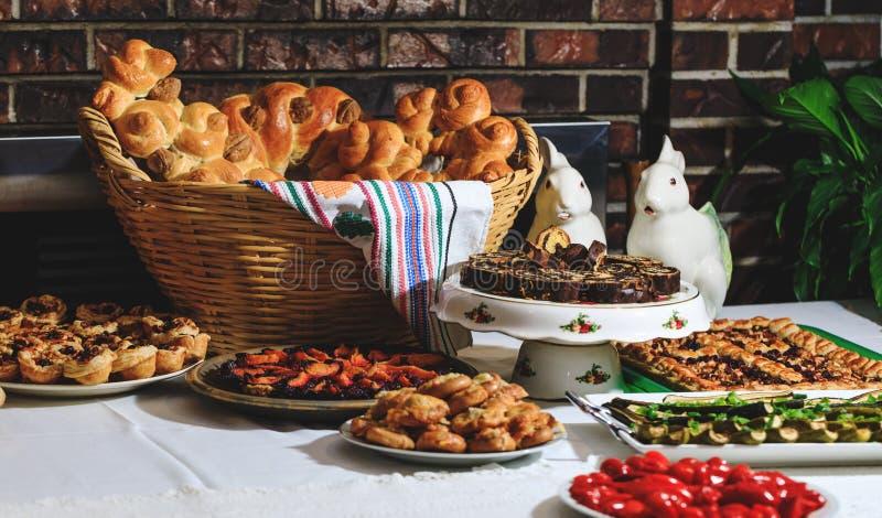 Osterferien-Tisch mit traditionelles Brot und authentisch rumänischer Küche Gebackene Brötchen, Colaci oder Kuchen in Strohkörben stockbilder