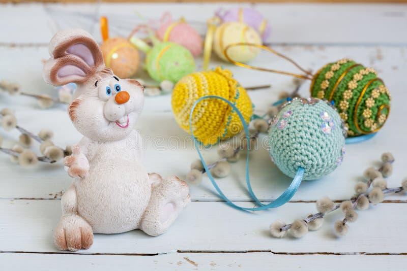 Osterhase, Pussyweide und handgemachte glückliche Ostereier auf einem hellen hölzernen Hintergrund lizenzfreie stockfotografie