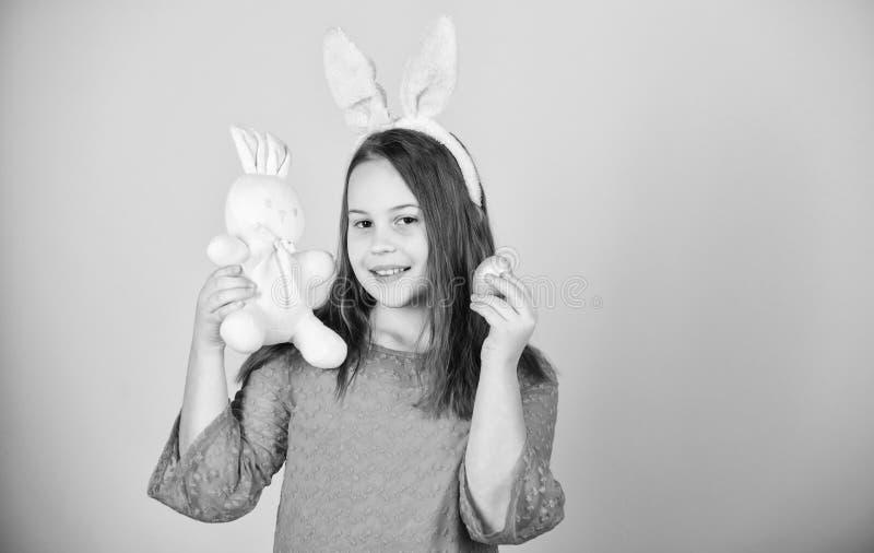 Osterhasen des M?dchens kleines Kinderzus?tzlicher Griff f?rbte Ei Ursprung von Osterhasen Ostern-Symbole und -traditionen playfu lizenzfreies stockbild