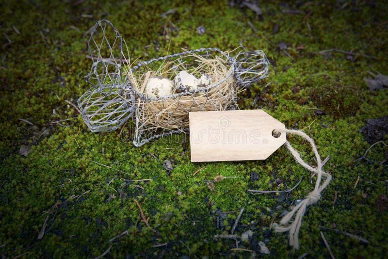 Osterhasenkorb mit hölzernem Tag stockbilder