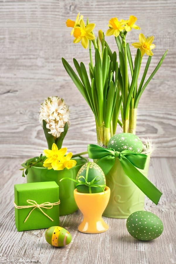 Ostern-Anordnung mit gelben Narzissen und farbigen Eiern lizenzfreies stockbild