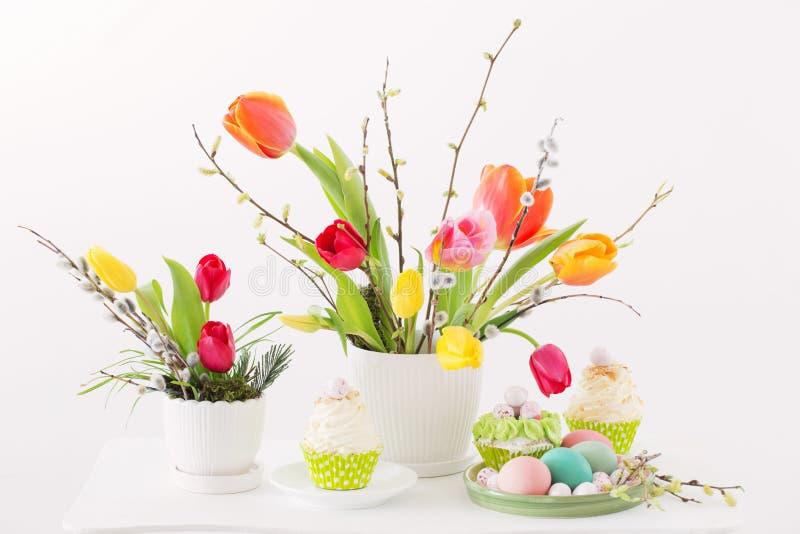 Ostern-Anordnung mit Tulpen und kleinen Kuchen stockbild