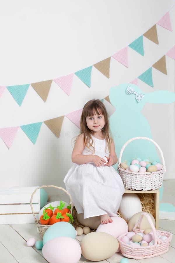 Ostern! Ein kleines Mädchen in einem weißen Kleid sitzt nahe einem Korb mit Eiern und einem Osterhasen Ostern-Standort, Dekoratio stockfoto