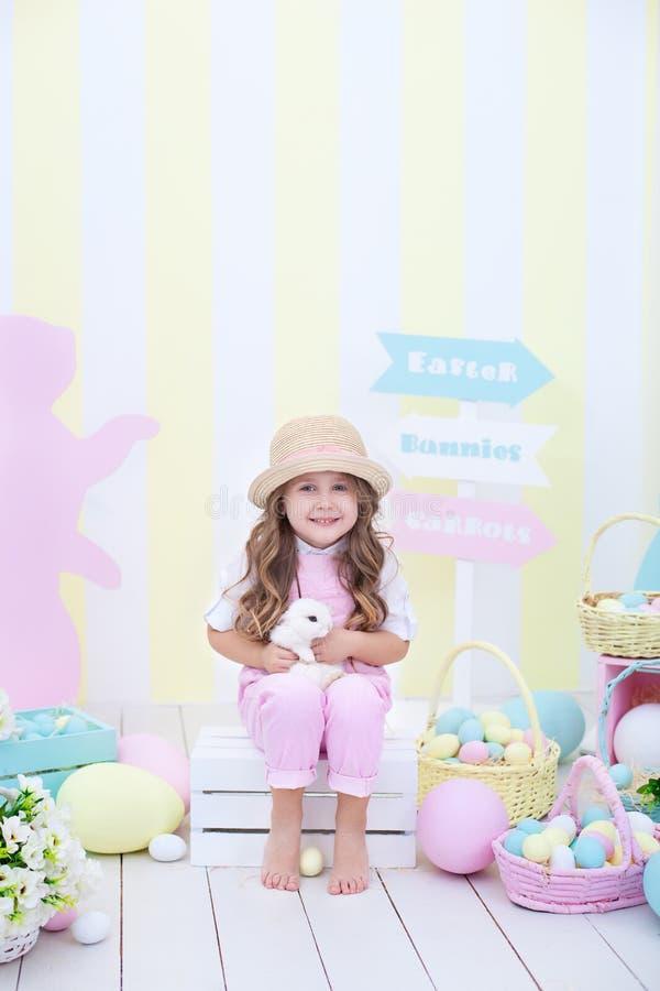 Ostern! Ein Mädchen spielt mit dem Osterhasen Ein Kind hält ein Kaninchen in seinen Armen vor dem hintergrund des Ostern-Innenrau stockfoto