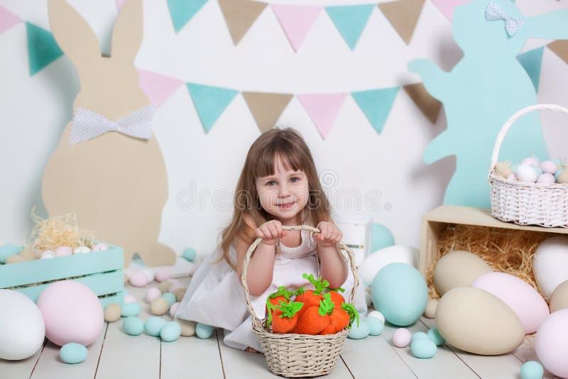 Ostern! Ein schönes kleines Mädchen in einem weißen Kleid sitzt mit einem Ostern-Korb und einer Karotte Kaninchen, bunte Ostereie lizenzfreie stockbilder