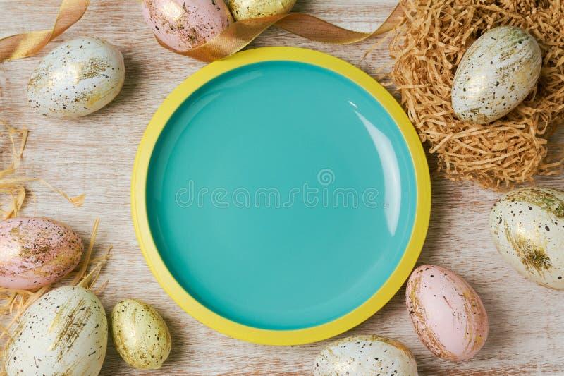 Ostern-Feiertagshintergrund mit leerer Platte und modernen Eidekorationen lizenzfreie stockfotos