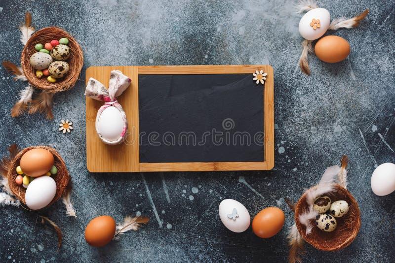 Ostern-Feiertagskarte mit verschiedenen Wachteln und Hühnereien auf rustikalem Hintergrund stockbilder