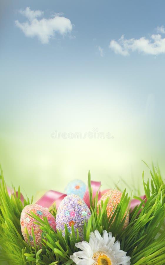 Ostern-Feiertagsszenenhintergrund Traditionelles gemaltes buntes Gras der Eier im Frühjahr über blauem Himmel stockbilder