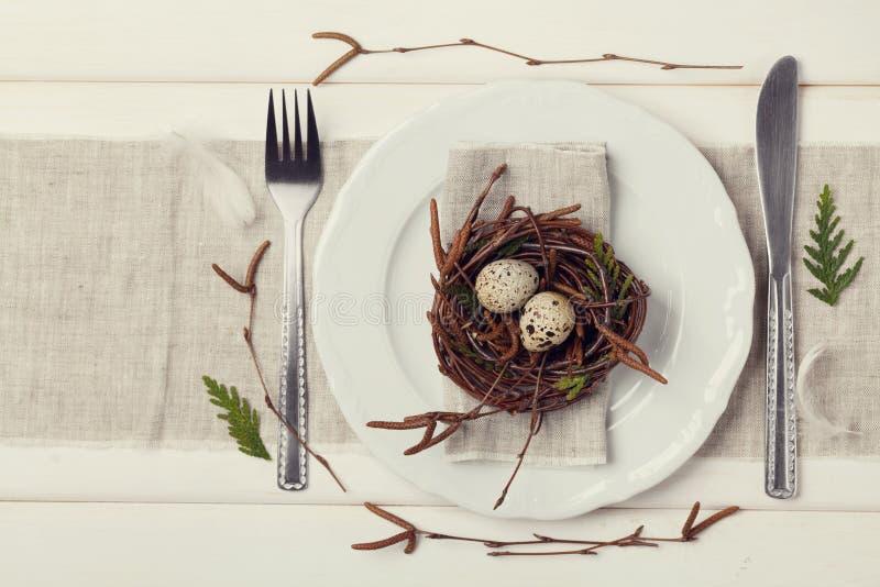 Ostern-Gedeck mit Eiern und Frühlingsdekoration auf rustikalem Hintergrund, Weinlesetonen stockfoto