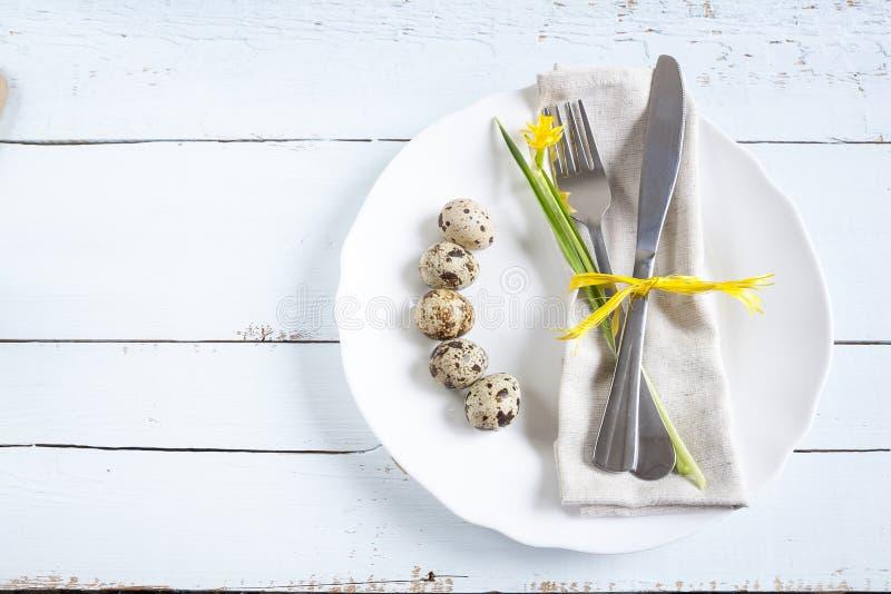 Ostern-Gedeck mit Frühlingsblumen, -eiern und -tischbesteck lizenzfreie stockbilder