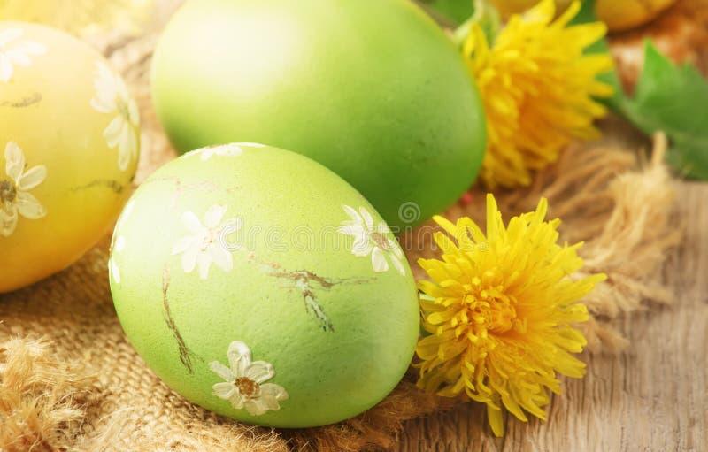 Ostern-Grün und gelbe gemalte Eier, gelbe Löwenzahnblumen auf festlicher Zusammensetzung des Frühlinges in der rustikalen Art, ru stockbild