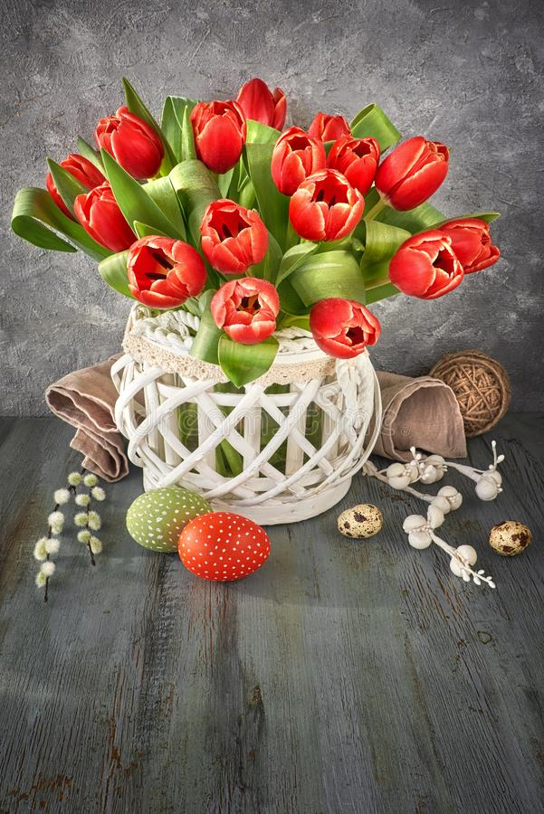 Ostern-Grußkartendesign mit Bündel roten Tulpen auf rustikalem b lizenzfreies stockbild
