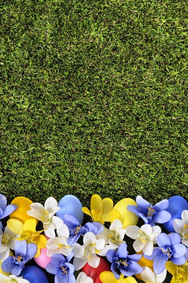 Ostern-Hintergrund mit Eiern und Blumen lizenzfreie stockfotografie