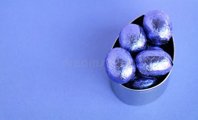 Ostern-Hintergrund mit purpurroten Schokoladeneiern in einer Metallovalform stockfotos