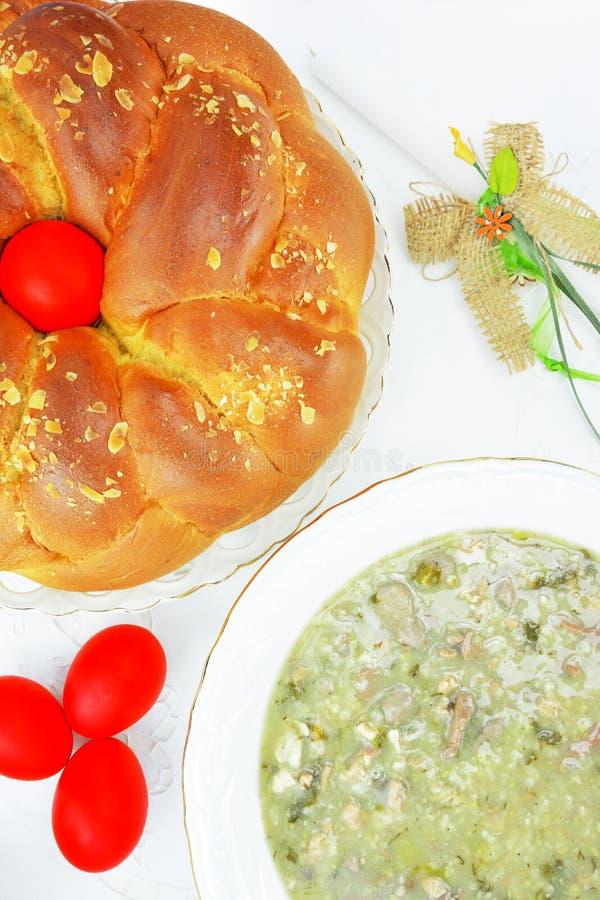 Ostern-Konzept mit Ostern-Kerze, roten Eiern, tsoureki und mayiritsa lizenzfreie stockfotos