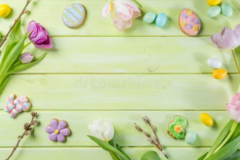 Ostern-Konzept - Plätzchen mit Blumen auf grünem hölzernem Hintergrund lizenzfreie stockfotografie