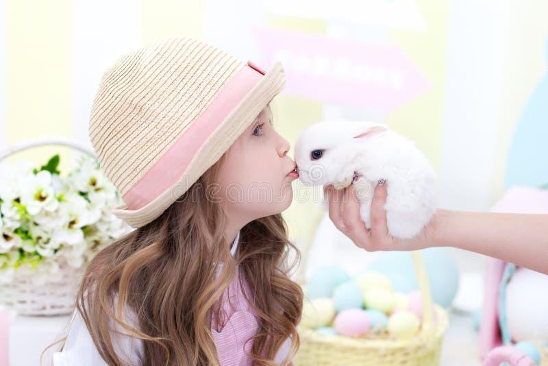 Ostern-Konzept und -Familienurlaub! Nettes Mädchen küssender Osterhase Bunter Dekor Ostern Kinderspiele mit einem flaumigen Kanin lizenzfreie stockfotografie