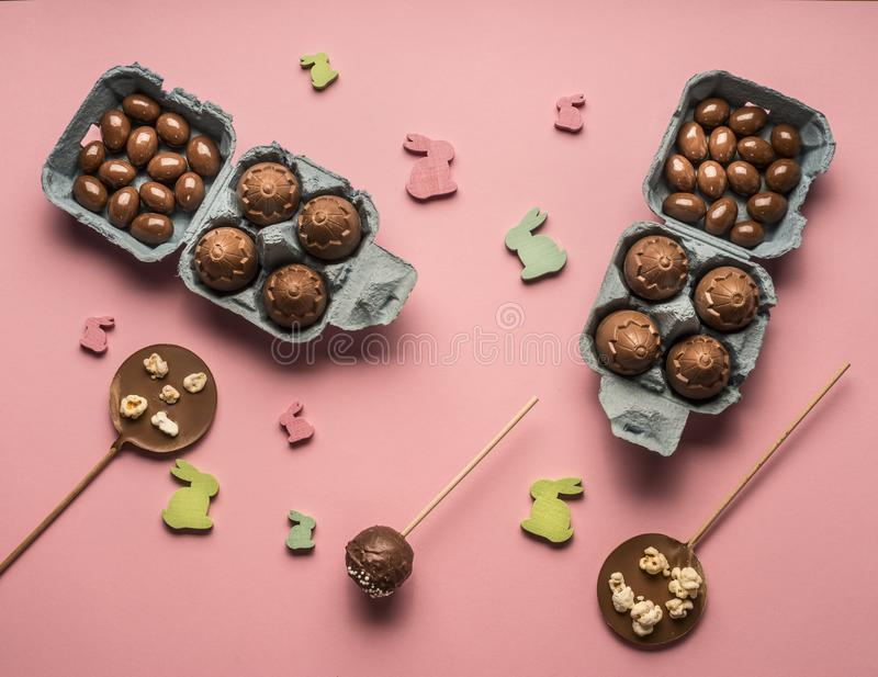 Ostern-Konzept, verschiedene Dekorationen, Schokoladeneier in einem Kasten, zeichnete auf einem rosa Hintergrund, Draufsichtebene stockbilder