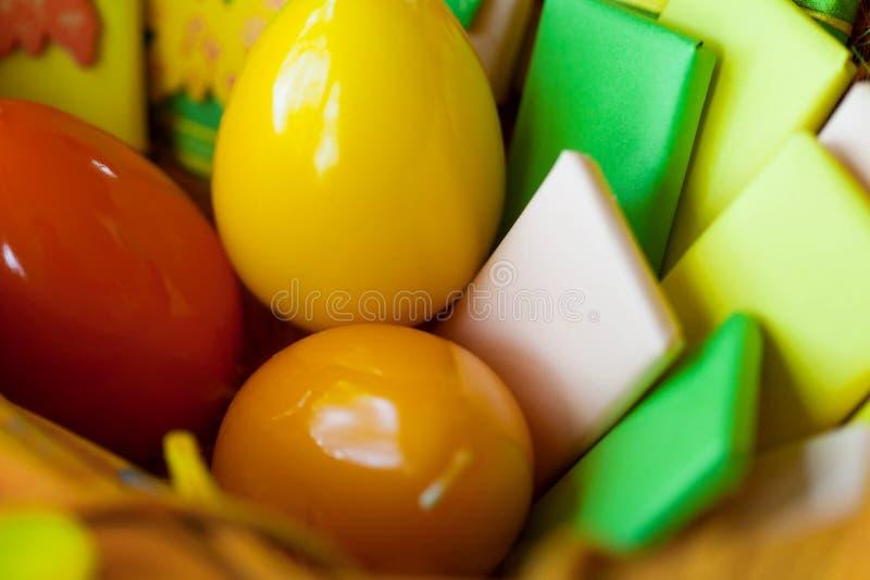 Ostern-Korb mit Eiern und eingewickelten Bonbons lizenzfreies stockbild