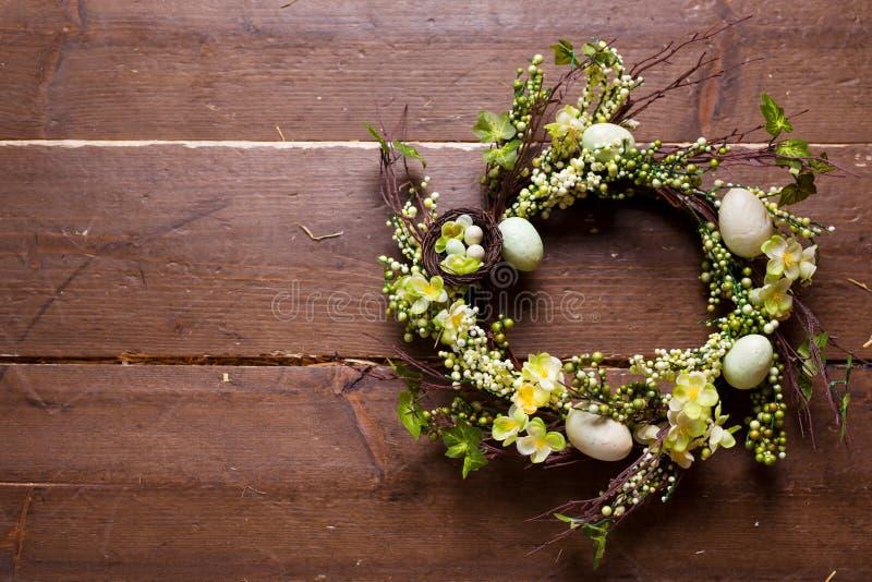 Ostern-Kranz mit Blumen und Eiern auf einem hölzernen Hintergrund lizenzfreie stockbilder