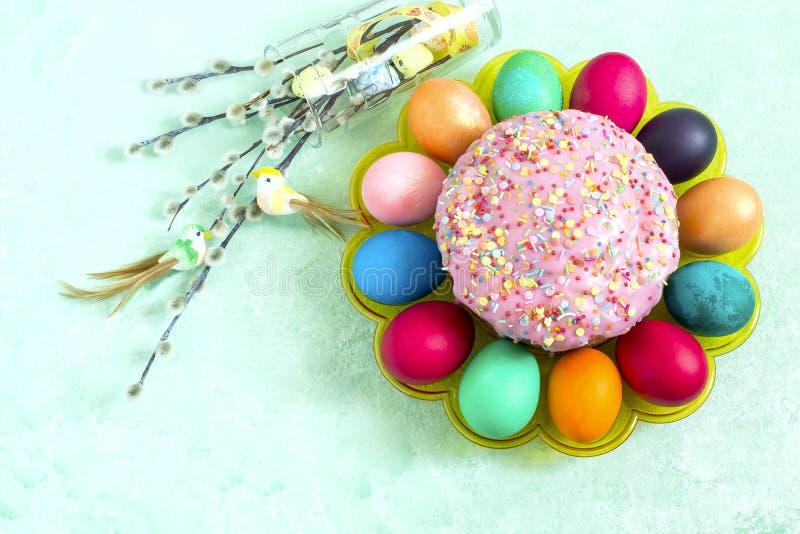 Ostern-Kuchen, gemalte Eier und Blumenstrauß der flaumigen Weide stockbild