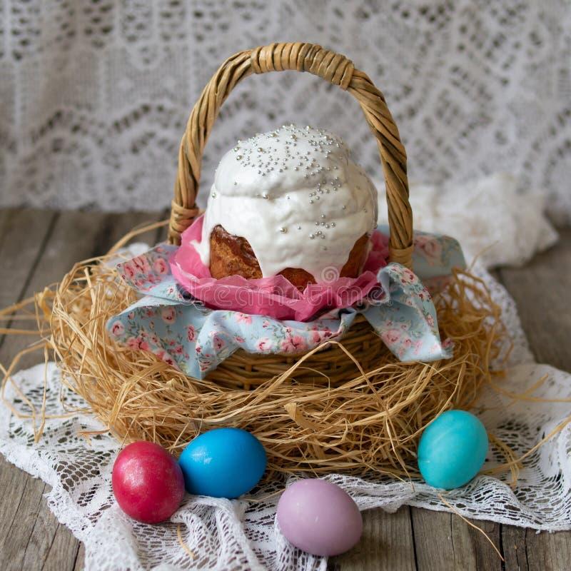 Ostern-Kuchen - kulich Traditionelles süßes Brot Ostern verzierte weiße Zuckerglasur im Strohkorb und farbige Eier auf Spitzeserv stockbilder