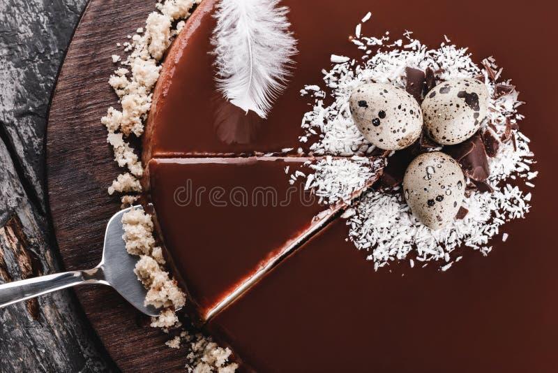Ostern-Kuchen mit Spiegelglasurschokolade, Kokosnuss, Frühlingsblumen, Wachteleier auf rustikalem Hintergrund Glückliche Ostern-F stockbild
