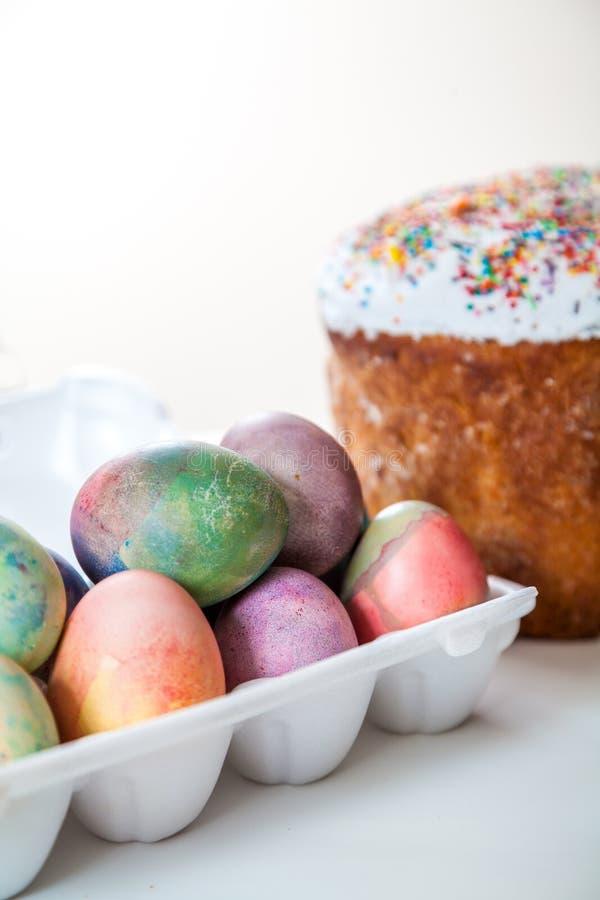 Ostern-Kuchen und bunte Eier im Behälter auf weißem Hintergrund lizenzfreie stockbilder