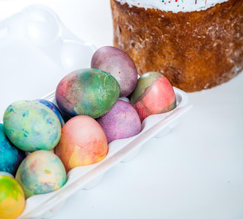 Ostern-Kuchen und bunte Eier im Behälter auf weißem Hintergrund lizenzfreie stockfotos