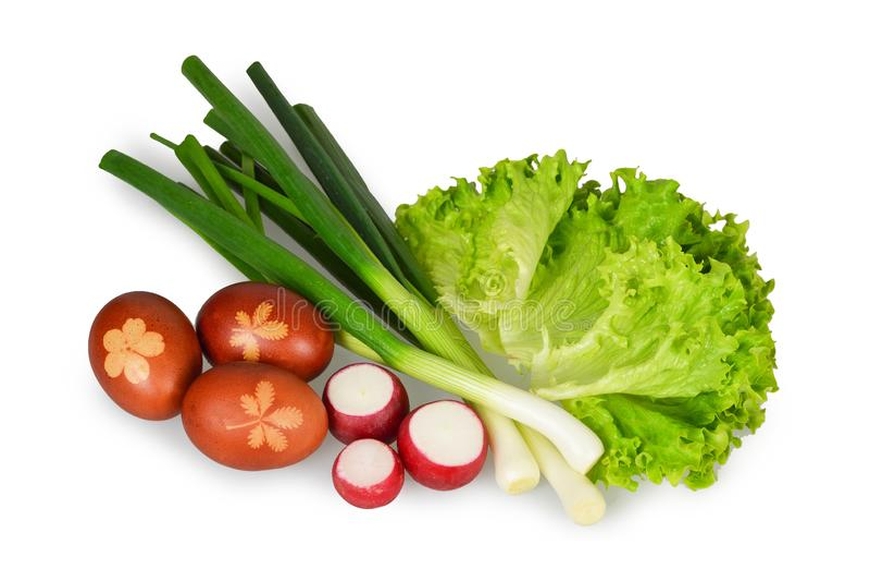 Ostern-Lebensmittel Frühlingszwiebeln, roter Rettich, Kopfsalat und farbige Ostereier lokalisiert auf Weiß lizenzfreie stockfotografie