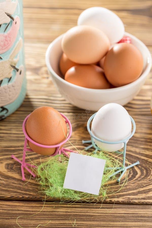 Ostern-Modellkarte mit Easter Eggs auf hölzernem Hintergrund für Saison-Ostern-Mitteilung mit blauem Vase stockfoto