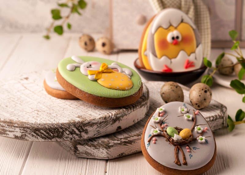 Ostern-Plätzchen mit gemaltem Osterhasen, Ostereiern und Huhn nahe dekorativem Buffet und Serviette stockfotos