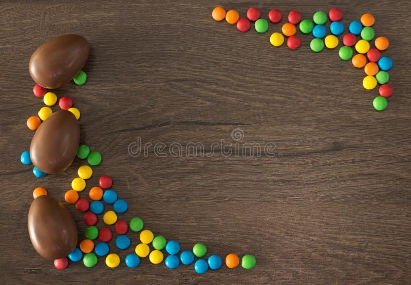 ostern Schokoladeneier mit mehrfarbigen S??igkeiten liegen auf einer h?lzernen braunen Tabelle stockfotos