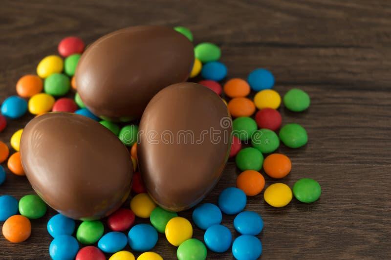 ostern Schokoladeneier mit mehrfarbigen S??igkeiten liegen auf einer h?lzernen braunen Tabelle lizenzfreies stockbild