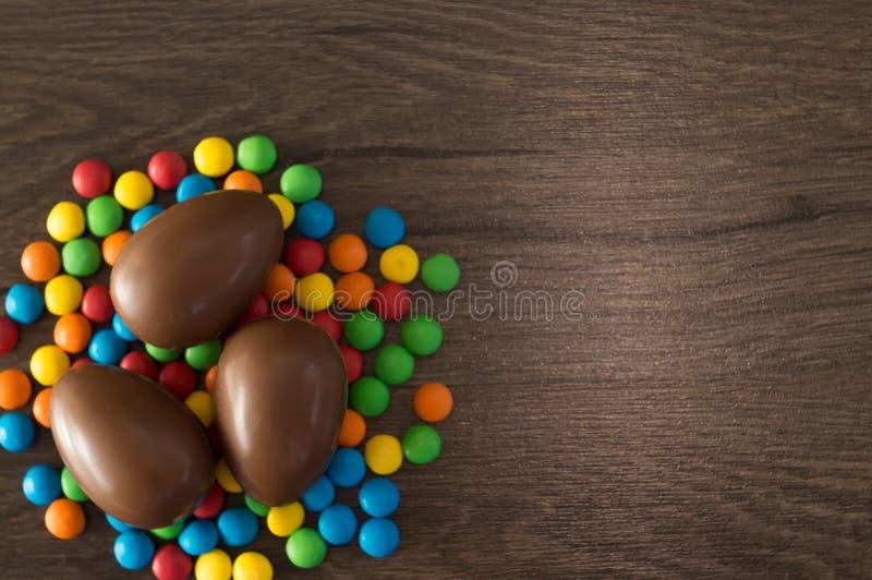 ostern Schokoladeneier mit mehrfarbigen S??igkeiten liegen auf einer h?lzernen braunen Tabelle stockbilder