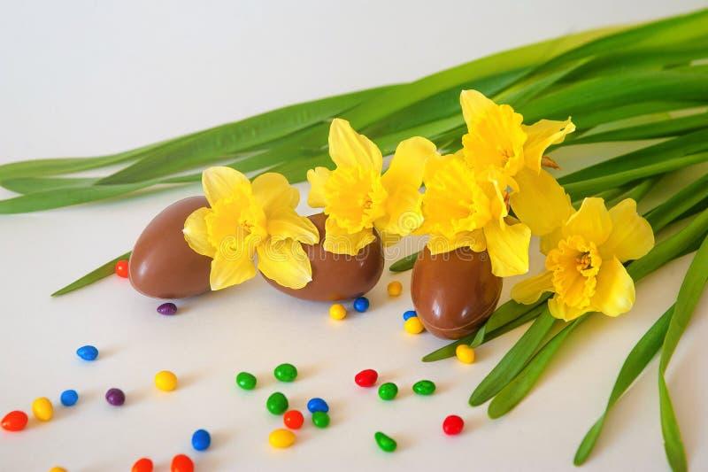 Ostern-Schokoladeneier und frische Frühlingsnarzissen auf verwittertem weißem Hintergrund Kopieren Sie Platz stockfotografie