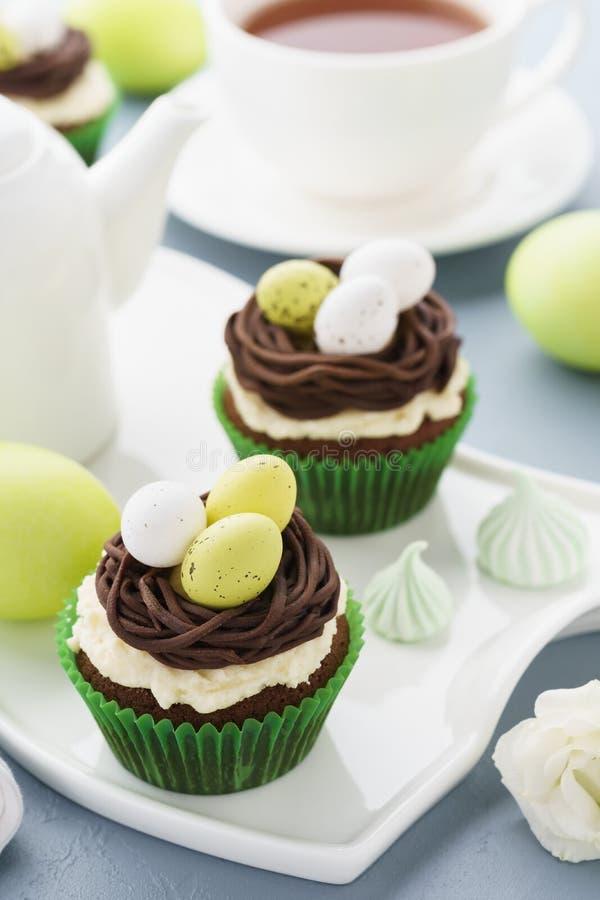 Ostern-Schokoladenkleine kuchen mit Nest, Süßigkeitseiern und Tee lizenzfreie stockfotos