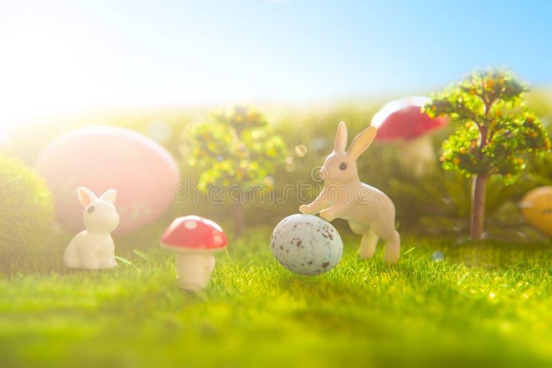 Ostern verzieren mit Kaninchenspielzeug und Ostereiern auf Rasenflächehintergrund lizenzfreies stockfoto
