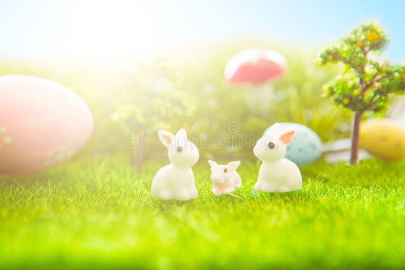 Ostern verzieren mit Kaninchenspielzeug und Ostereiern auf Rasenflächehintergrund stockfotos