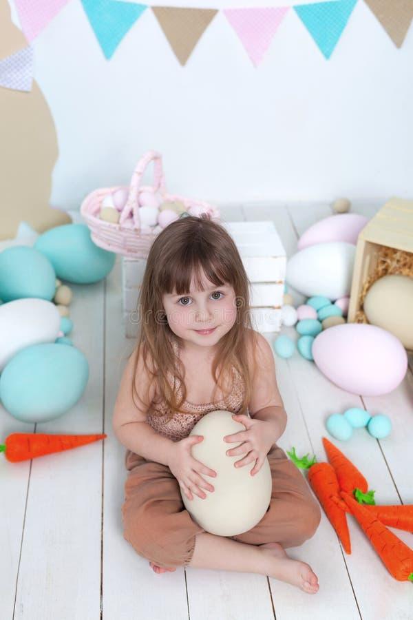 Ostern! Wenig Mädchen im Overall sitzt mit einem großen Osterei Ostern-Standort, Dekorationen Familienurlaube, Traditionen bunt stockfotografie